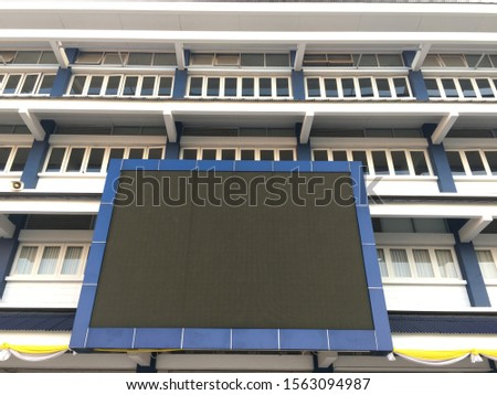 Blank scoreboard in front of a school building providing frame for space for runaround or wraparound text  #1563094987