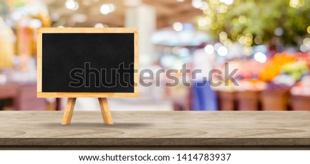 Blank screen blank blackboard on wooden table top with blur supermarket grocery bokeh background,Mock up for display or montage of design #1414783937