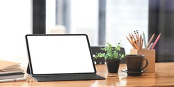 Blank screen computer tablet with keyboard case putting on wooden working desk with pencil holder, coffee cup, potted plant, stack of books and pen over neat living room as background.