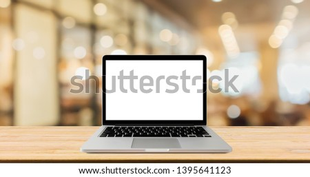 Blank screen laptop computer on wood table top with blur cafe restaurant with abstract bokeh light defocused background #1395641123