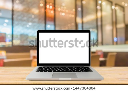 Blank screen laptop computer on wood table top with blur cafe restaurant with abstract bokeh light defocused background