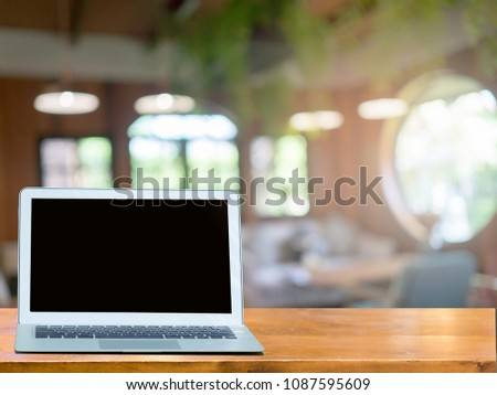 Blank screen Laptop on wooden table blurred cafe or restaurant background.