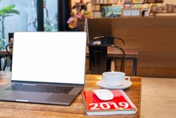 Blank screen laptop with mouse and coffee cup and notebook with Year 2019 calculator on table in cafe.
