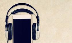 Blank screen modern smartphone on the desk with headphones