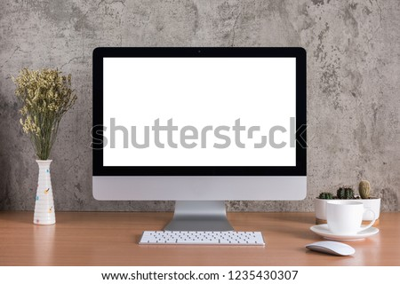 Blank screen of all in one computer with dry flowers, coffee cup and cactus vase on raw concreate background #1235430307