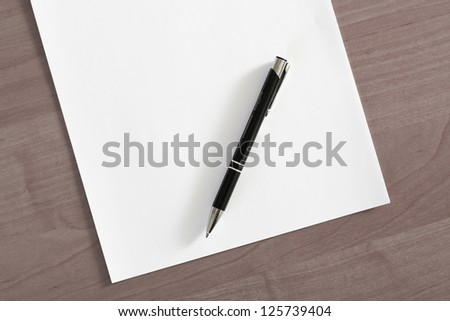 Blank sheet of paper and a pen on the table
