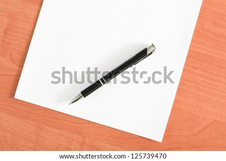 Blank sheet of paper and a pen on the table - stock photo