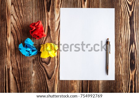 Blank sheet of paper and pen on bright wooden office desk