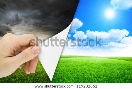 Blank sheet of paper with hand opening it. Storm changes to good weather. Nature background