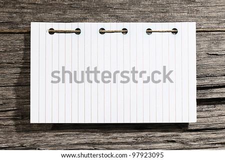 Blank sheet of paper with rope on wooden background.