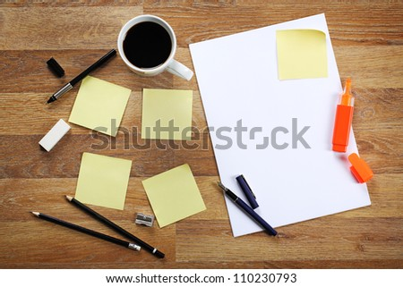 Blank sheet of paper, yellow sticky notes, cup of black coffee, pencil and pen on wooden office desk.