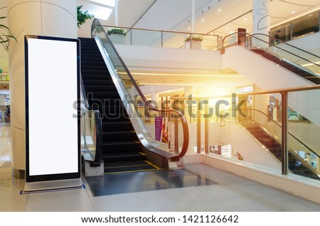 blank showcase billboard or advertising light box for your text message or media content with escalator in modern department store shopping mall, shopping center, commercial and marketing concept