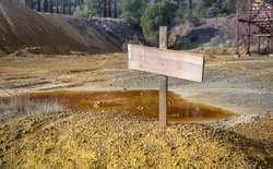 Blank sign on top of chemical waste pile with an abandoned mine quarry and rusty machinery, selective focus