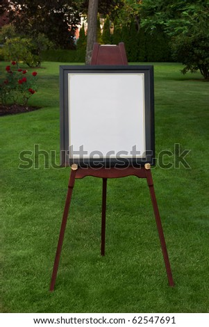 Blank sign sits on easel in garden.