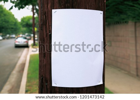 Blank sign stapled to a telephone pole #1201473142