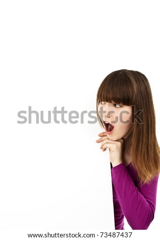 Blank sign. Surprised young female looking at white billboard . Isolated on white background.