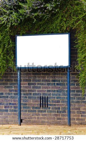Blank sign surrounded by textured brick wall and green foliage.