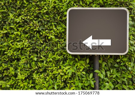 Blank Sign with arrow on green leaves wall
