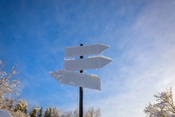 Blank signpost with three white arrows against blue sky in sunny frozen day. Blank track pointers or guide post on winter background with copy space. Icicles on signpost in sunlight. Christmas card