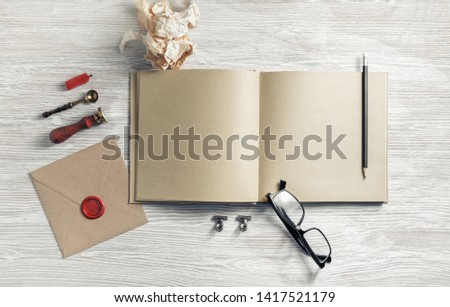 Blank sketchbook and retro stationery on light wooden background. Flat lay.