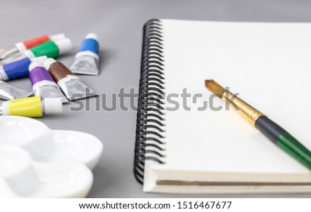 Blank sketchbook on grey background with brush, ceramic palette and watercolor tube