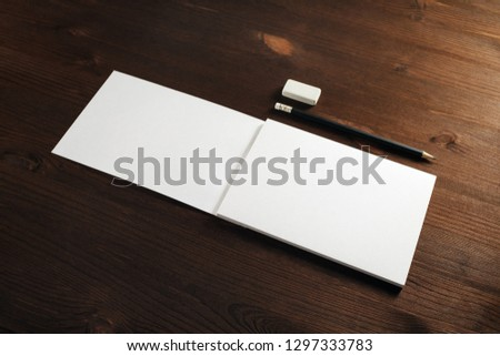 Blank sketchbook or album for drawing, pencil and eraser on wooden background. Responsive design template. Space for text.