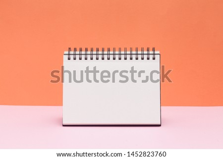 Blank sketchbook or calendar concept on colored background. Empty notepad on pink and orange background.