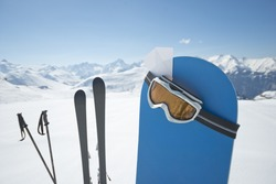 Blank ski pass and winter sport equipment such as ski and snowboard waiting on top of mountain ready for you. Concept to illustrate ski admission fee