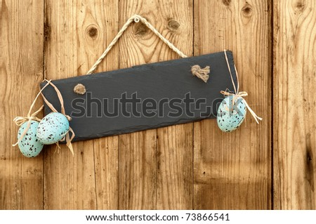 Blank slate sign hanging on wooden background with Easter eggs