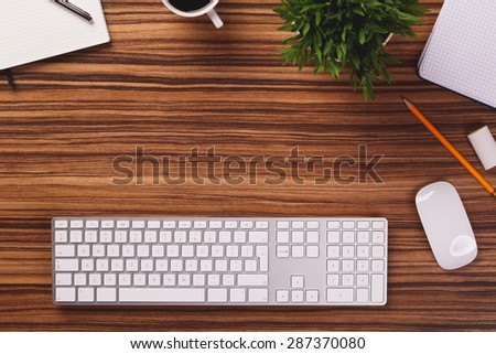 Blank space between modern white keyboard, mouse, pencil, mug of coffee, plant and other office equipment on dark wooden office desk.