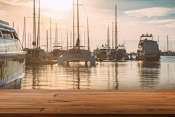 Blank space of wooden plank floor at marina, blurred background of sea, yachts and sunset sky. Warming looks view of yacht dock.