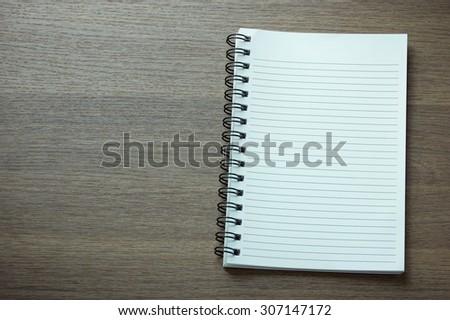 blank spiral notebook on dark wood background