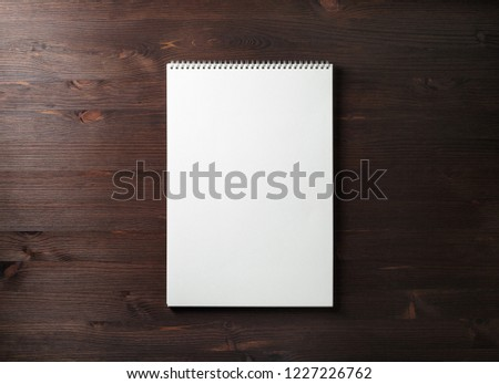 Blank spiral sketchbook on wood table background. Responsive design template. Space for text. Flat lay.