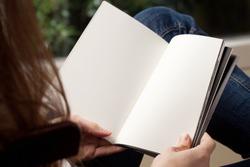 Blank spread, open book in woman's hands
