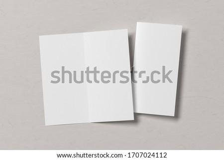 Blank square leaflet on white wooden background. Bi-fold or half-fold opened and folded brochure isolated with clipping path. View directly above. 3d illustration