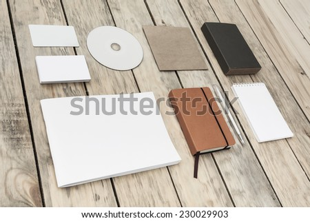 Blank stationery set on old wood background: business cards, plastic card, booklet, notebook, notepad, CD, box and pen. Vintage style