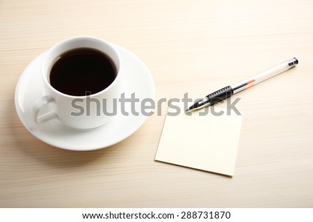 Blank sticky note is on the table with ball pen and coffee aside.