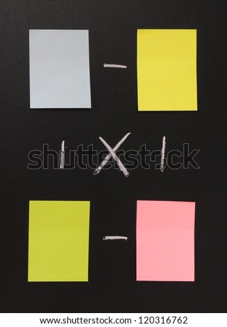 blank sticky notes in different colors on a blackboard - stock photo