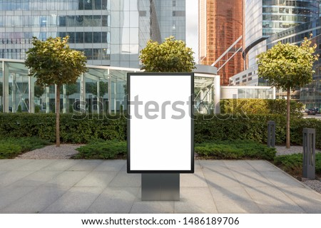 Blank street billboard poster stand mock up on city business district with skyscrapers on background. 3d illustration.