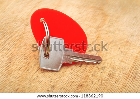 Blank tag and a key on wooden background