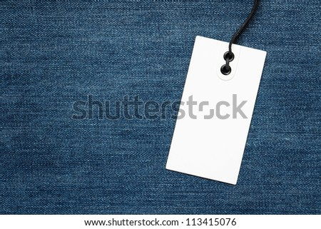 Blank tag over denim background with copy space