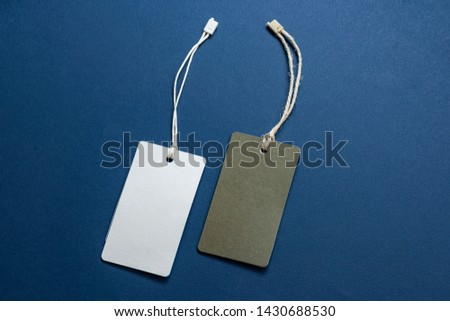 Blank tags tied with string. Price tag, gift tag, sale tag isolated on blue background.