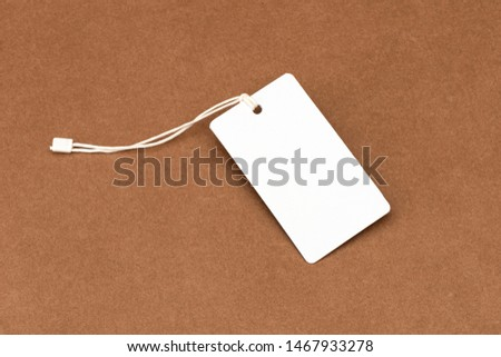 Blank tags tied with string. Price tag, gift tag, sale tag isolated on craft background.