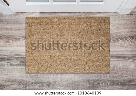 Blank tan colored coir doormat before the white door in the hall. Mat on wooden floor, product Mockup - Shutterstock ID 1010640109