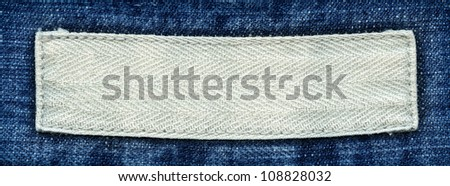 Blank textile label  sewed on a blue jeans. Can be used as background for your text.