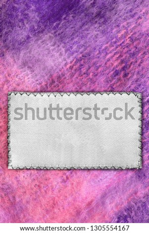 Blank textile patch on purple mohair background closeup