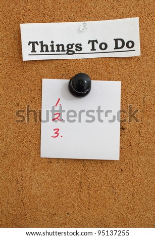 Blank to do list note pinned to a cork bulletin board with a giant push pin.