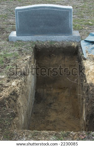 blank tombstone with room for text in front of open grave