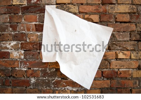 Blank torn paper poster on an old brick wall
