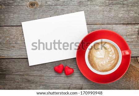 Blank valentines greeting card and red coffee cup on wooden background
